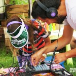 Teacher instructing child how to produce electronic music.